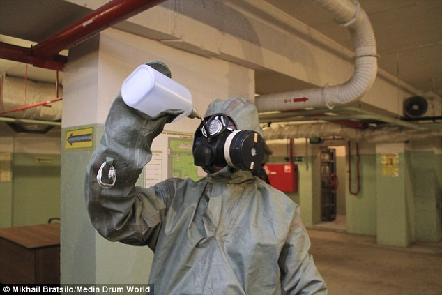 23736c1d00000578-2847238-safety_first_a_man_demonstrates_one_of_the_bunker_s_radiation_su-22_1416834615833