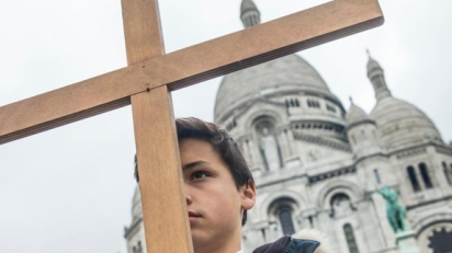 Boy stands with cross in front of Sacre Coeur basilica in Paris