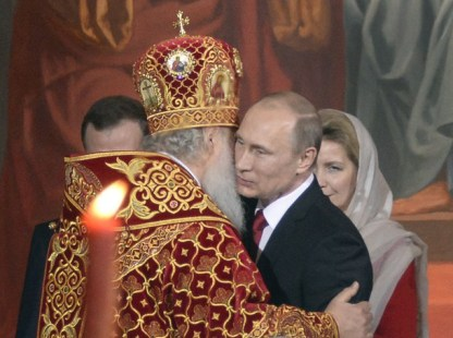 Russian Orthodox Patriarch Kirill (L) congratulates Russian President Vladimir Putin during a service for the celebration of the Orthodox Easter in Moscow, early on April 20, 2014. AFP PHOTO/ ALEXANDER NEMENOV
